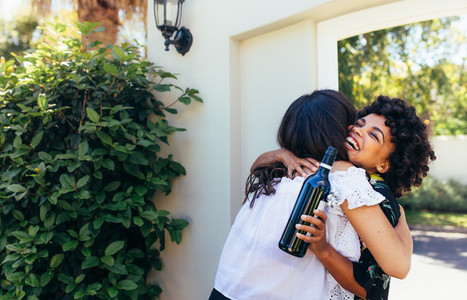 Woman with wine bottle congratulating friend for new house