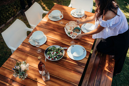 Woman setting food on table for housewarming
