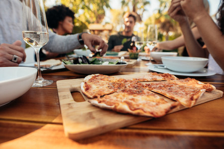 Pizza on dining table with friends