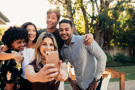 Group of friends at housewarming party taking selfie
