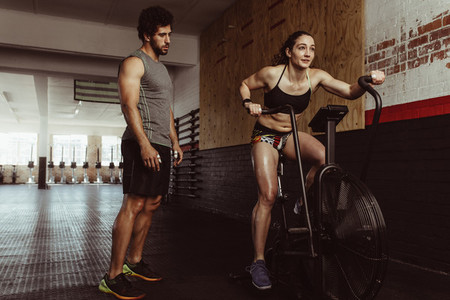 Female doing cardio workout at gym with trainer