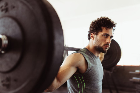Healthy young guy at gym exercising with barbell