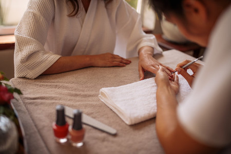 Woman getting her nails done by a manicurist