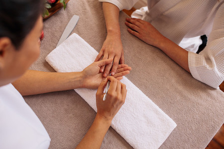 Woman hands receiving manicure and nail care procedure