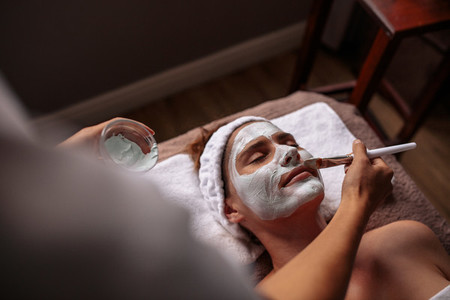 Cosmetician applying facial mask on female face