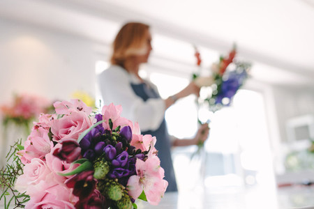 Flower bouquet in front with florist working in background
