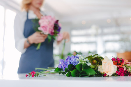 Fresh flower on counter with florist at back