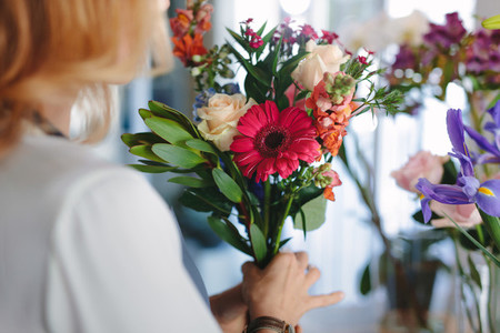 Mixed flowers in hands on female florist