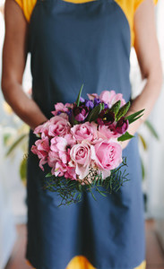 Female florist holding mixed flower bouquet