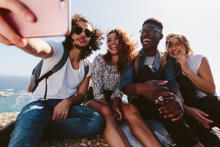 Group of hikers relaxing and taking selfie