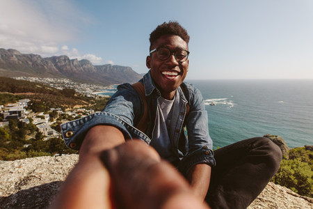 Smiling african guy on top of a mountain taking selfie