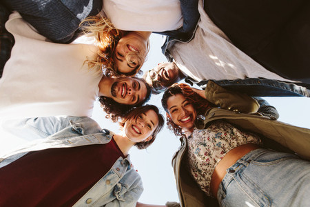 Cheerful group of friends huddling outdoors