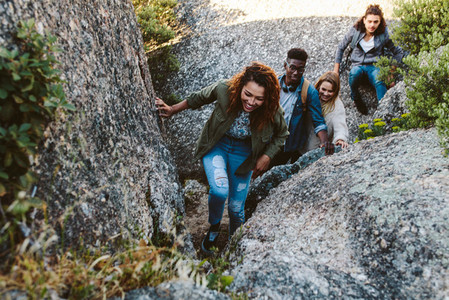 Woman climbing mountain rocks with friends