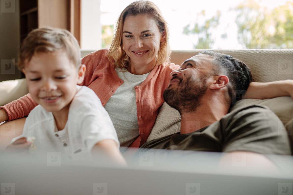 44c32aaf8c9 Photos - Happy young family relaxing on couch at home - YouWorkForThem