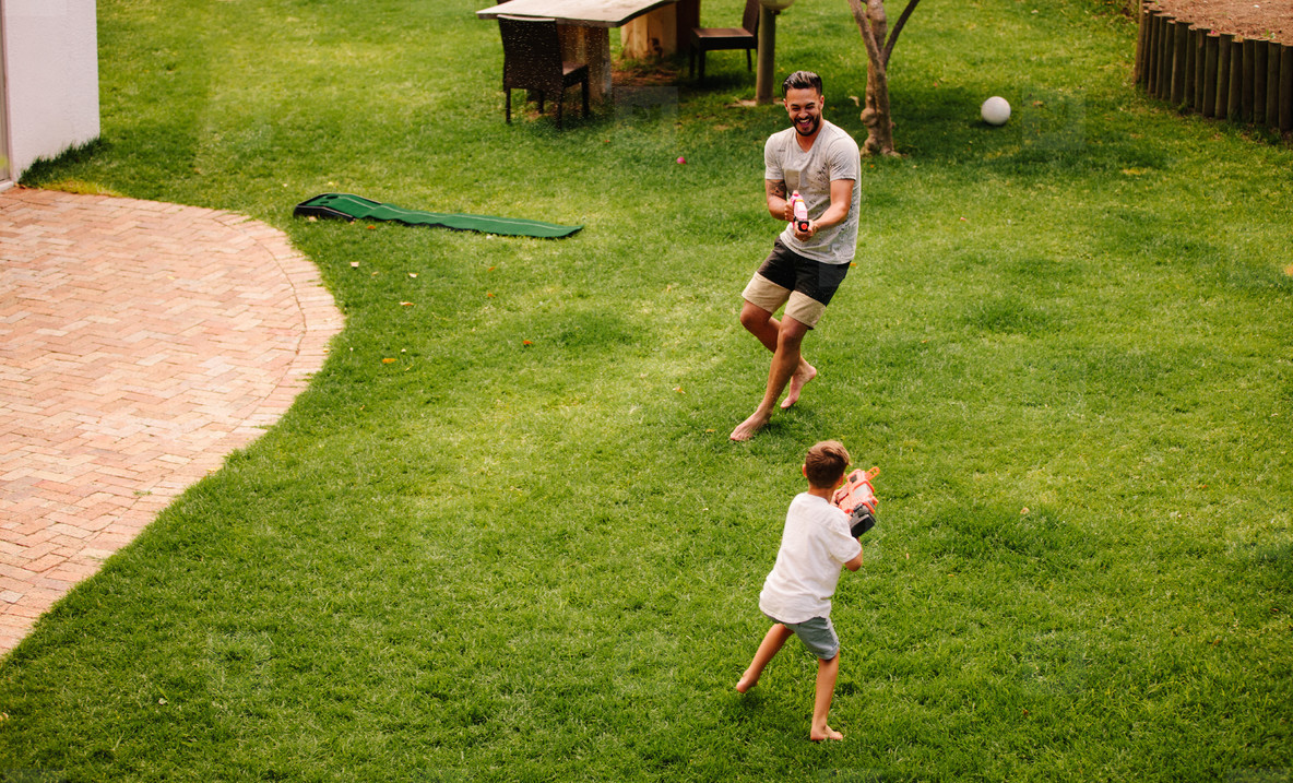 Father and son having fun with water guns outdoors