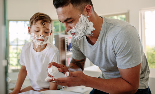 Father and son applying shaving foam on their faces