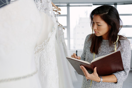 Female dressmaker working in bridal wear store