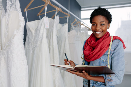 Wedding dress designer working in her boutique