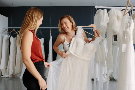 Store assistant helps the bride in choosing perfect attire