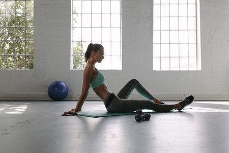 Woman relaxing at fitness club after training session