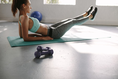 Fit woman doing stretching exercise mat at gym