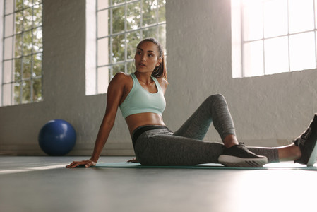 Female athlete sitting on exercise mat at fitness club