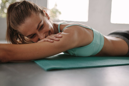 Happy young woman resting after exercise session at gym