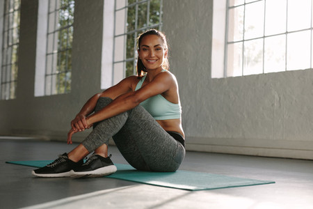 Woman relaxing on exercise mat and smiling