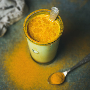 Golden milk with turmeric powder in glass  square crop