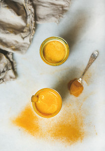 Golden milk with turmeric powder in glasses over grey background
