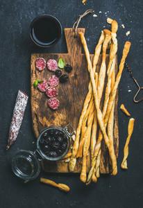 Grissini bread sticks  sausage  black olives  wine over dark background