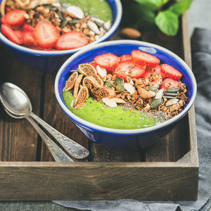 Green smoothie bowls with seeds  nuts and fruit  square crop