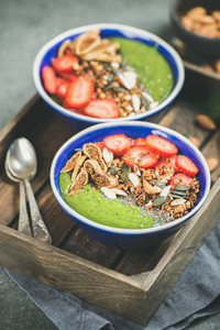 Green smoothie bowls with strawberries  granola  seeds  fruit  nuts
