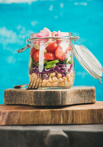 Vegetable and chickpea sprout vegan salad jar  blue wall background