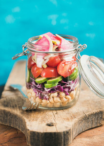 Vegetable and chickpea sprout vegan salad in jar blue background