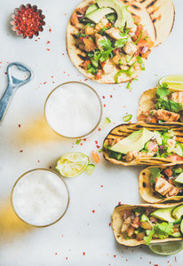 Healthy corn tortillas with chicken  vegetables and beer in glasses