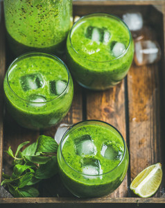 Fresh smoothie with ice cubes mint lime in wooden tray
