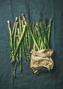 Fresh green asparagus in craft paper bag over grey cloth