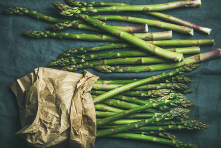Fresh green asparagus in craft paper bag over grey background