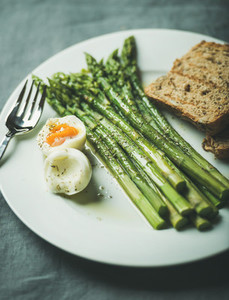 Cooked asparagus with soft boiled egg  grilled bread toasts and herbs