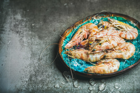 Raw uncooked tiger prawns on chipped ice  concrete background