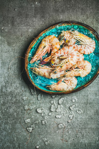 Raw uncooked tiger prawns on chipped ice  grey concrete background