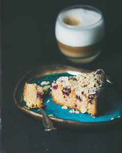 Piece of lemon ricotta almond raspberry cake and latte