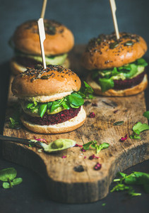 Healthy vegan burger with beetroot quinoa patty arugula on board