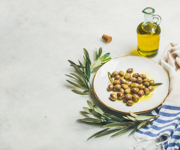 Pickled green Mediterranean olives  olive tree branch and virgin oil