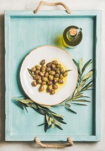 Pickled green Mediterranean olives  olive tree branch  virgin oil