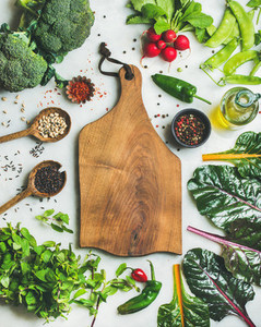 Fresh greens raw vegetables and grains wooden board in center