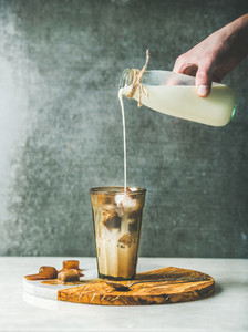 Mans hand pouring milk to Iced latte caramel coffee cocktail