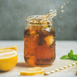 Iced tea with fresh herbs in jar with splashes