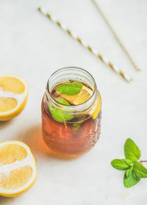 Summer cold Iced tea with lemon slices and fresh herbs
